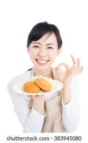 young woman with apron holding croquette, isolated on white background