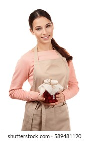 Young woman in apron holding jar with jam on white background
