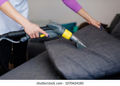 Young woman in apron washing sofa with vacuum washer. Maid cleaning at home