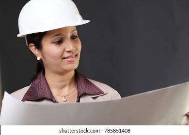 Young woman architect looking at blue print