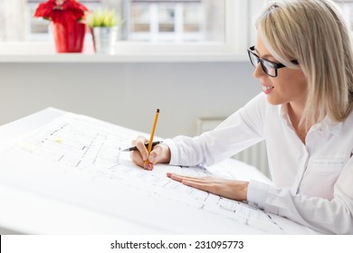Young woman architect working on architectural blueprints