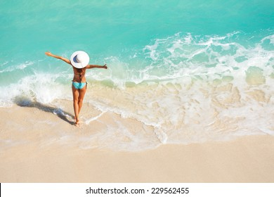 Young woman with arms apart on sand beach