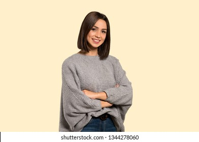 Young woman with arms crossed and looking forward on isolated yellow background