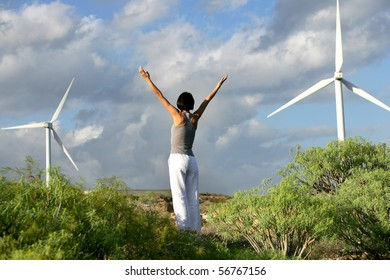 Young woman with arms up in front of a wind turbine