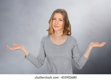 young woman with arms out shrugs shoulders