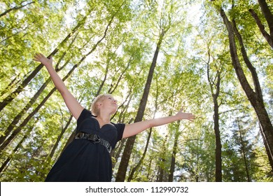 Young woman with arms raised enjoying  in green forest