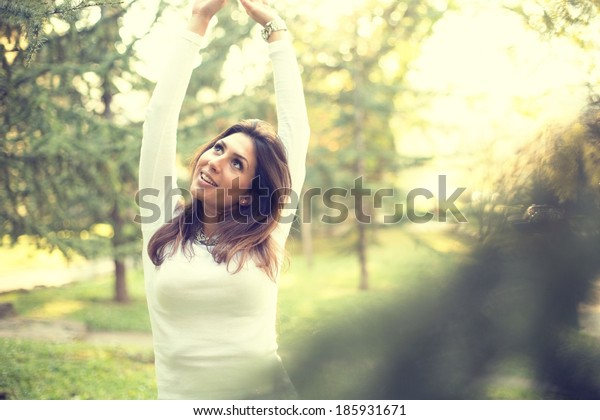 Young woman arms raised enjoying the fresh air in green park