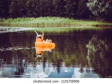 Young woman arms raised up feeling free, happy and relaxed, enjoy life on inflatable blow up orange chair floating on lake pond in nature outdoors in summer. Childhood memories concept.