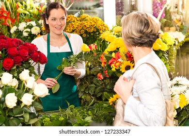 Young woman arranging flowers shop market selling customer smiling