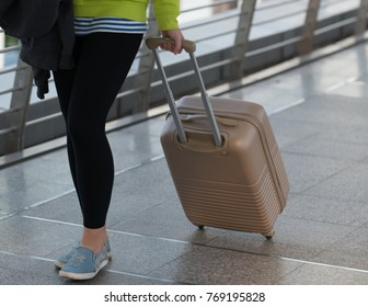 young woman arrived from trip. He is walking from airport with luggage