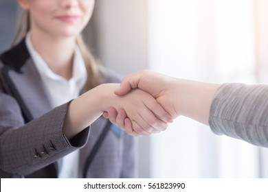 Young woman arriving for a job interview. Business people handshake in modern office. Greeting deal concept close up.