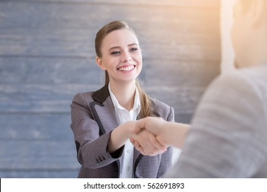 Young woman arriving for a job interview. Business people handshake in modern office. Greeting deal concept