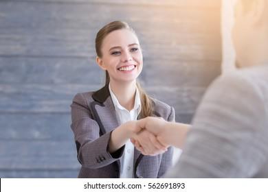 就職面接に来る若い女性。現代のオフィスでは、ビジネスマンが握手する。グリーティングデールのコンセプト