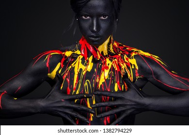 Young woman with art fashion makeup. An amazing woman with black, yellow and red paint makeup