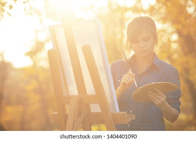 young woman artist drawing a picture on canvas on an easel in nature, a girl with a brush and a palette of paints working inspired by autumn, a concept of creativity and a hobby