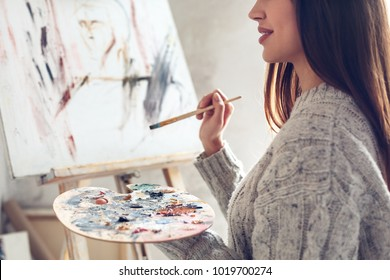 Young woman artist painting at home creative holding palette close-up