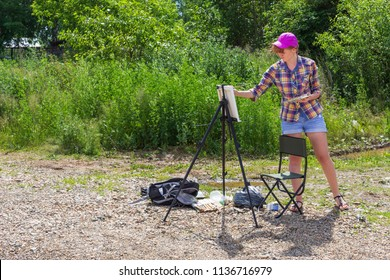 A young woman artist painting standing at the easel outdoors.