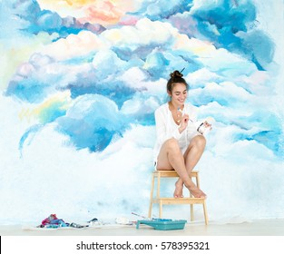 Young woman artist. She painting a sky on the wall.