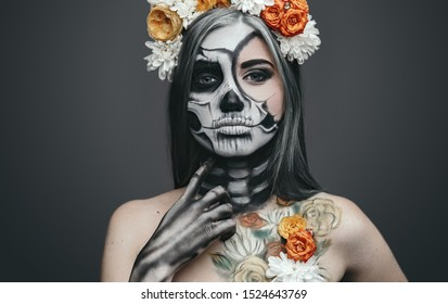 Young woman with artistic spooky makeup and fresh flowers on head standing prepared for Halloween party touching painted neck and looking at camera