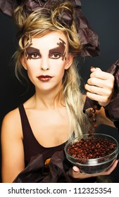 Young woman with artistic visage and with cafe seeds in glass plate