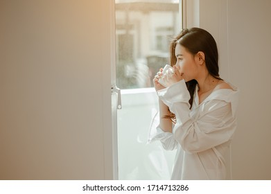 Young woman asia wake up refreshed in the morning and relaxing eat coffee, cornflakes, bread and apple for breakfast at house on holiday. Asian, asia, relax, breakfast, refresh, lifestyle concept.