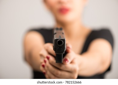 young woman asian girl holding a gun aiming at the gun, with selective focus