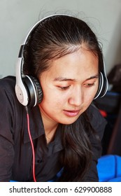 Young woman asian listening to music in earphones from smartphone