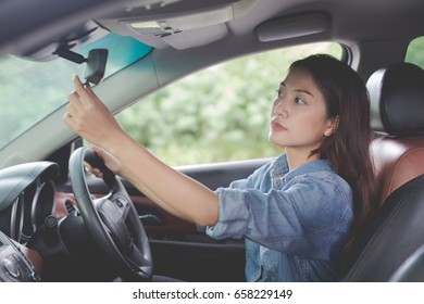 Young woman Asian looking in the rearview mirror of a car