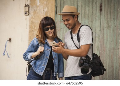 Young woman ask directions from a young man.with smartphone