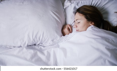 Young woman asleep peacefully in her bed one morning