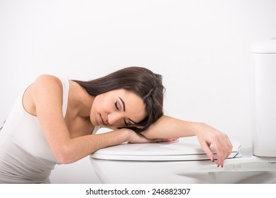 Young woman asleep in the toilet. White background.