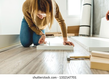 Young woman assembling furniture in new house