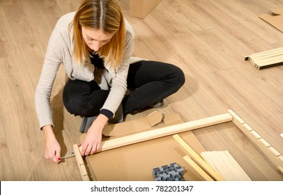 Young woman assembling furniture in new apartment