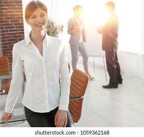 young woman assistant standing near desktop.