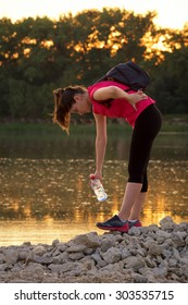 Young woman athlete with back pains during the workout. She is sitting near a lake in the evening with a bottle of water in the hand.