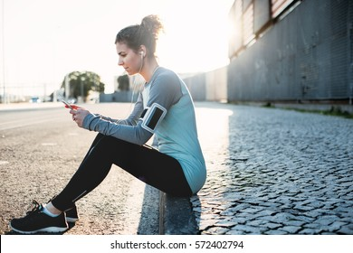Young woman athlete resting on the street with music and mobile phone in hands. Urban workout with smart gadgets and sport applications