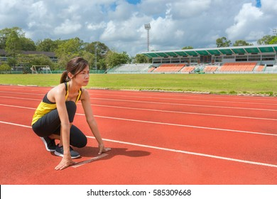 Young woman athlete at starting position ready to start a race. Female sprinter ready for sports exercise on racetrack, Healthy lifestyle and sport concept, Selective focus