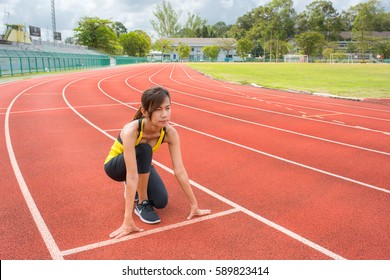 Young woman athlete at starting position ready to start a race. Female sprinter ready for sports exercise on racetrack