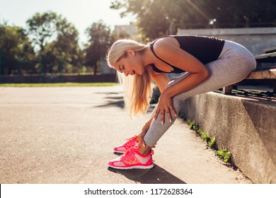 Young woman athlete touching her ankle after running on sportsground in summer. Injury during training. Pain in leg. Hurt knee
