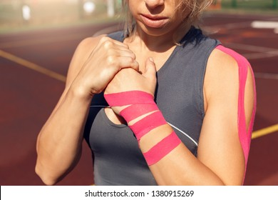 Young woman athlete wearing kinesio muscle tape on arm standing on stadium sporty lifestyle looking down thoughtful close-up