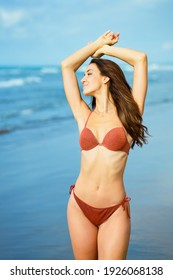 Young woman with athletic body on a tropical beach wearing red bikini