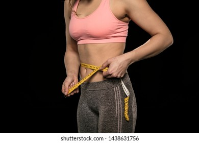 young woman with an athletic body uses a measuring tape