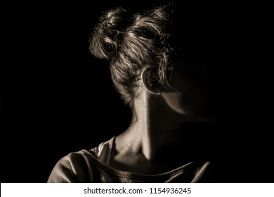 A young woman in athletic wear and a messy bun is shown from shoulders up. Shoulders square to camera and head turned, facing right.  A dark shadow hides face. Sepia edit against black background.
