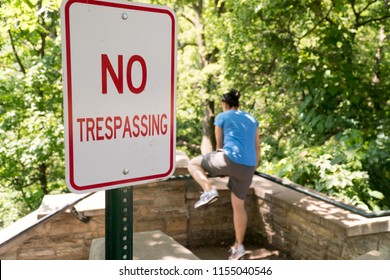 Young woman attempt to jump over railing into restricted area labelled by no trespassing sign. Private property deep woods and forest area illegal to walk past signage