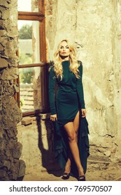Young woman with attractive face blonde hair fashion makeup dressed in green sexy dress posing on old window and stone wall