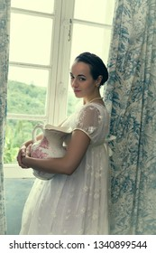 Young woman in authentic regency dress near a window of a classical interior