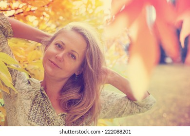 Young woman with autumn leaves and fall garden background