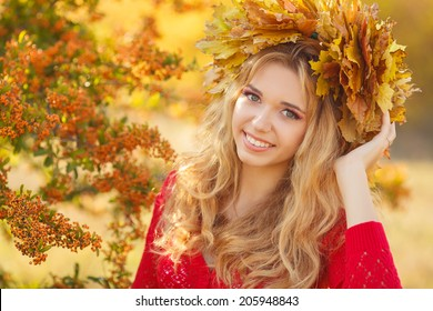 Young woman with autumn leaves in hand and fall yellow maple garden background. Woman with wreath of yellow leaves on head. Autumn bright portrait.