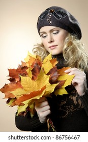 Young woman with autumn leaves in hand