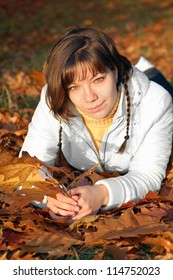Young woman with autumn orange leaves in forest